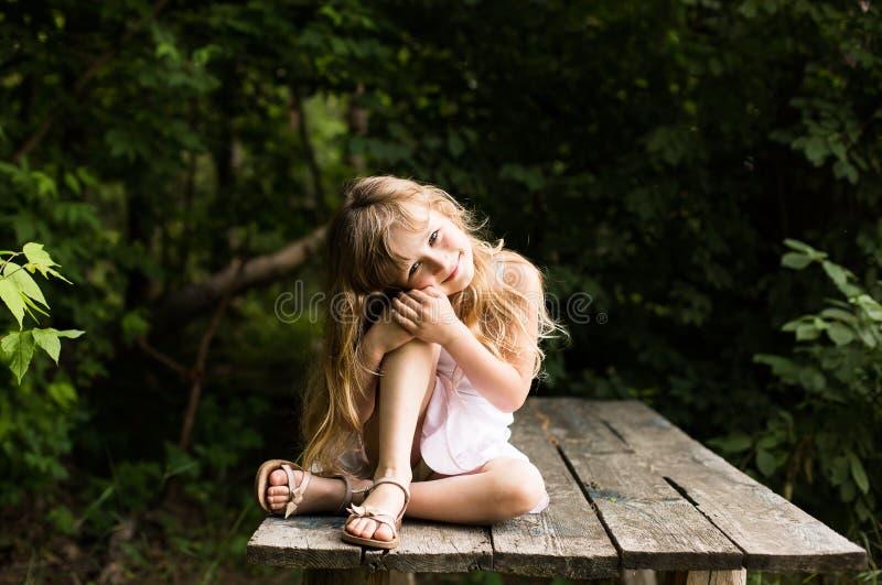 Vrij het glimlachen peinzende meisjeszitting op de oude brug royalty-vrije stock foto's