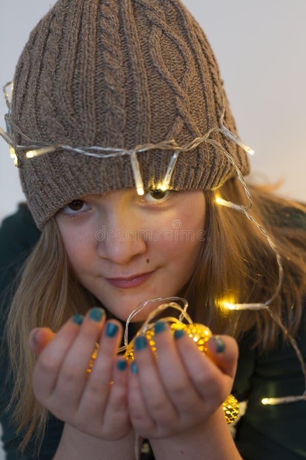 Vrij het jonge meisje dragen breit hoed en het houden van verlichte slinger van lichten stock foto's