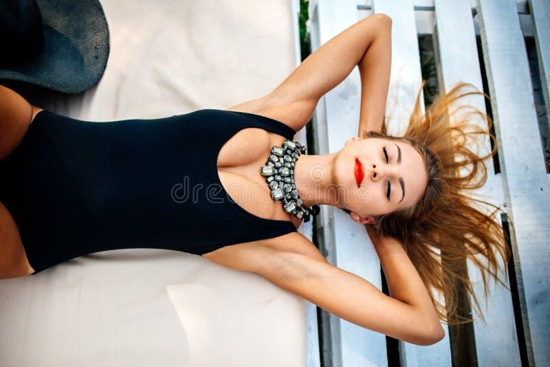 Vrij het jonge meisje ontspannen openlucht in zwarte swimwear royalty-vrije stock afbeelding