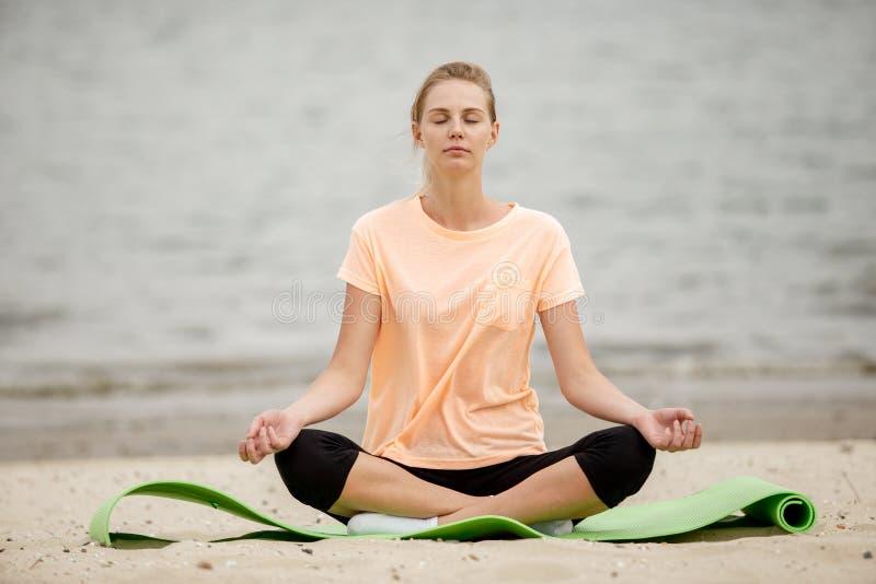 Vrij het jonge meisje ontspannende situeren in de lotusbloempositie inzake een yogamat op zandig strand op een warme dag stock foto's