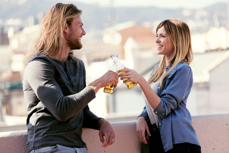 Vrij het jonge paar roosteren met flessenbier terwijl het kijken thuis elkaar op het dak stock fotografie