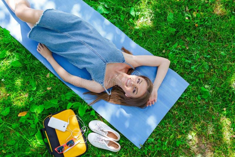 Vrij het jonge vrouw ontspannen op het gras in een park Hoogste mening royalty-vrije stock foto's