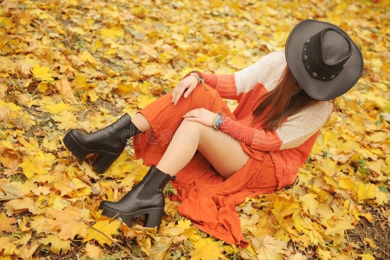Vrij het jonge vrouw stellen in de herfstpark, leerhoed royalty-vrije stock fotografie