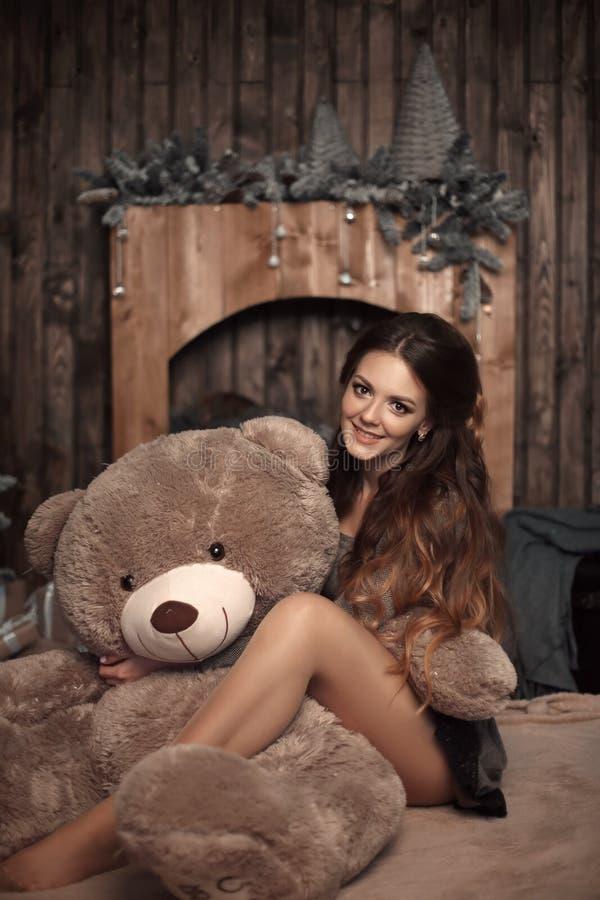 Vrij het leuke donkerbruine meisje stellen met grote teddybeer op floo royalty-vrije stock afbeeldingen