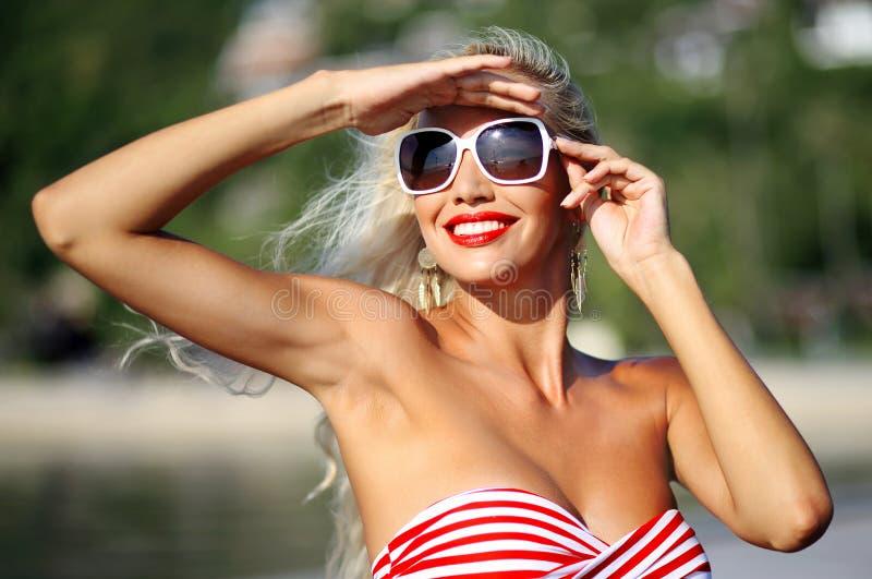 Vrij het modieuze jonge het glimlachen blondevrouw stellen dichtbij het overzees royalty-vrije stock afbeelding