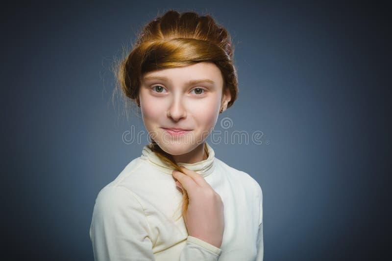 Vrij het roodharige meisje spelen met haar die haar op grijs wordt geïsoleerd royalty-vrije stock afbeeldingen