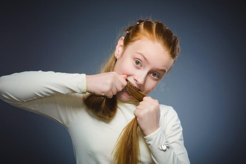 Vrij het roodharige meisje spelen met haar die haar op grijs wordt geïsoleerd stock foto