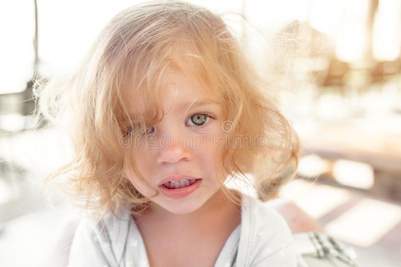 Vrij jong close-upportret van weinig blond bleek ongelukkig humeurig kindmeisje die zonder vrienden droevig in camera op vage zon royalty-vrije stock fotografie