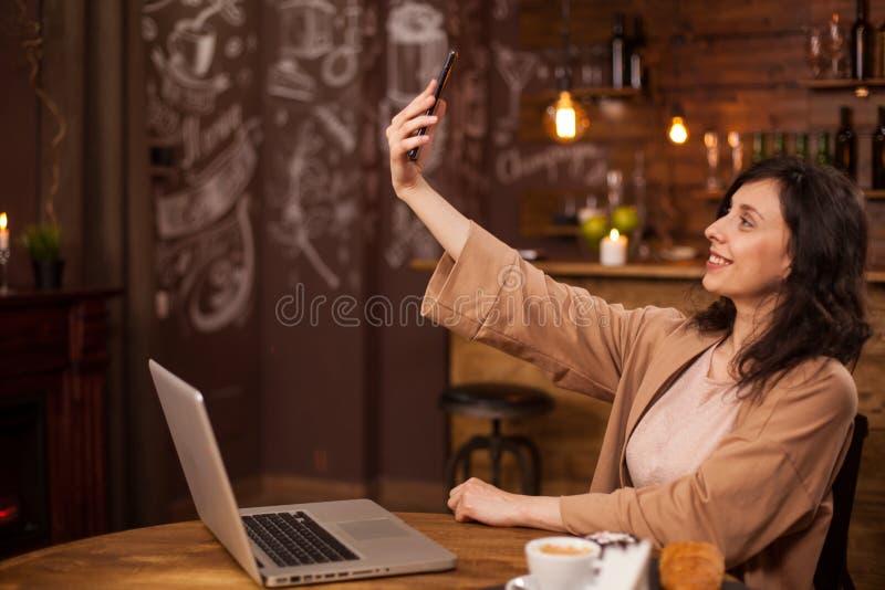 Vrij jong meisje die een selfie met haar mobiele telefoon in een moderne koffiewinkel spreken stock afbeeldingen