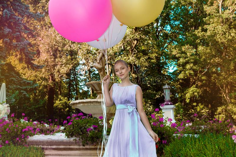 Vrij jong meisje die met grote kleurrijke ballons in het park dichtbij de stad lopen - beeld stock fotografie