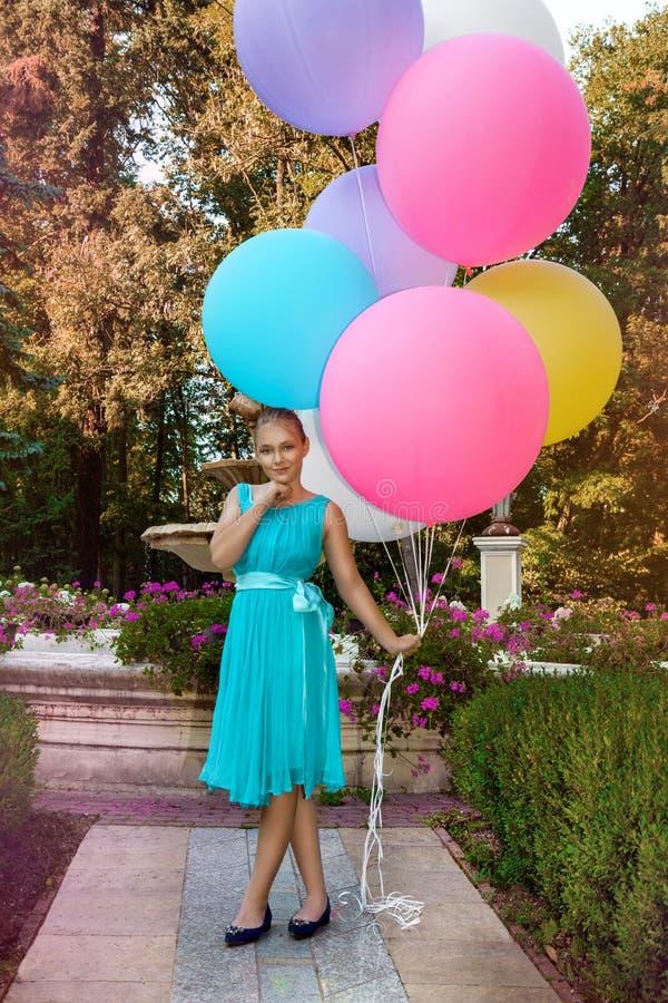 Vrij jong meisje die met grote kleurrijke ballons in het park dichtbij de stad lopen - beeld stock foto