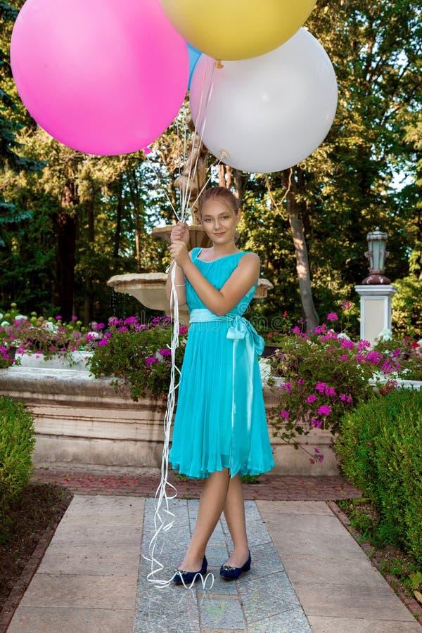 Vrij jong meisje die met grote kleurrijke ballons in het park dichtbij de stad lopen - beeld royalty-vrije stock foto