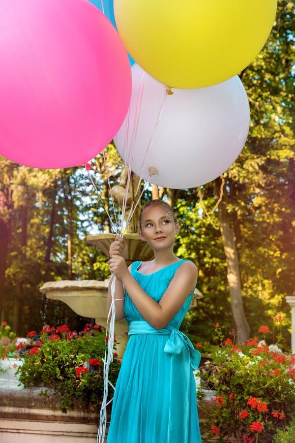 Vrij jong meisje die met grote kleurrijke ballons in het park dichtbij de stad lopen - beeld royalty-vrije stock fotografie