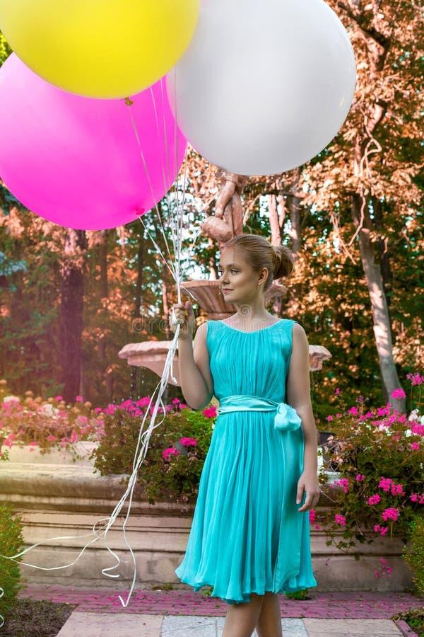 Vrij jong meisje die met grote kleurrijke ballons in het park dichtbij de stad lopen - beeld stock afbeelding