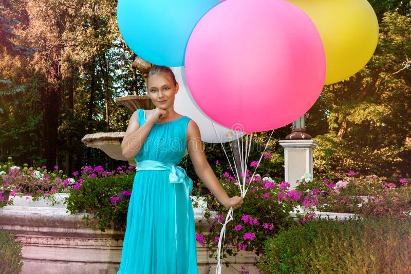 Vrij jong meisje die met grote kleurrijke ballons in het park dichtbij de stad lopen - beeld royalty-vrije stock afbeelding