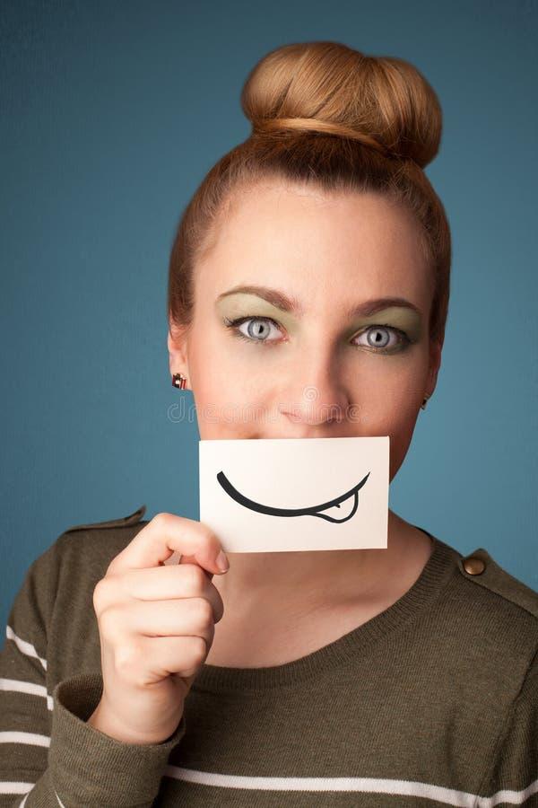 Vrij jong meisje die witte kaart met glimlachtekening houden royalty-vrije stock fotografie