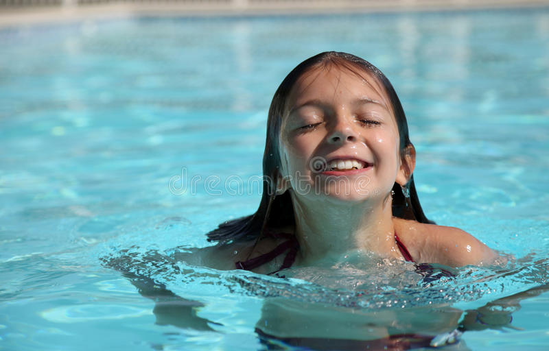 Vrij jong meisje in een zwembad stock fotografie