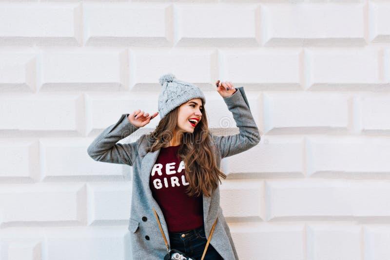 Vrij jong meisje in grijze laag op grijze muurachtergrond Zij draagt gebreide hoed, houdt handen lucht, kijkt gelukkig stock foto