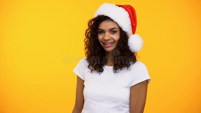 Vrij jong wijfje die in santahoed op camera op heldere achtergrond, partij glimlachen stock afbeeldingen