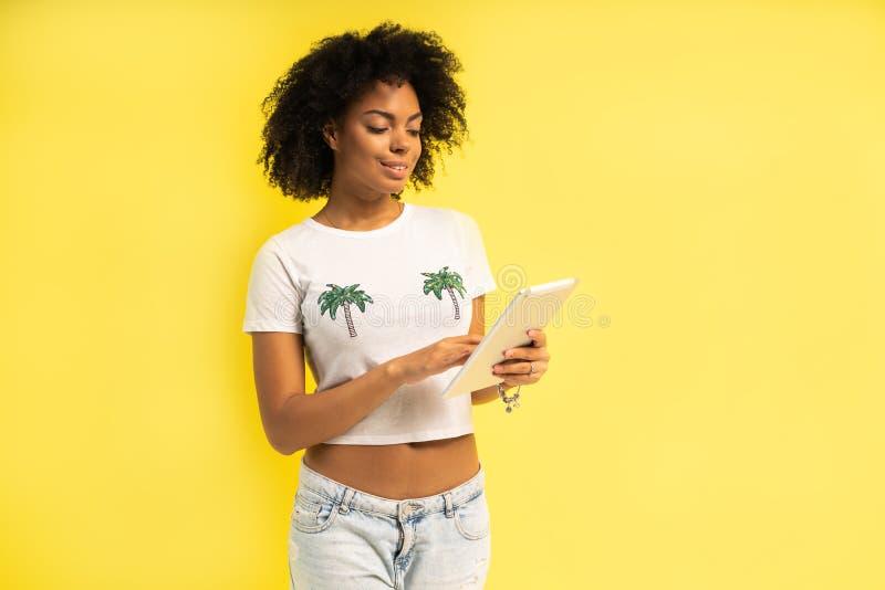 Vrij jonge afro Amerikaanse vrouw die die en tabletcomputer bevinden met behulp van over gele achtergrond wordt geïsoleerd stock foto's