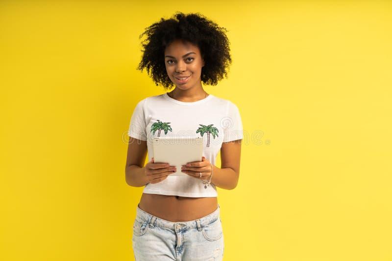 Vrij jonge afro Amerikaanse vrouw die die en tabletcomputer bevinden met behulp van over gele achtergrond wordt geïsoleerd royalty-vrije stock afbeelding