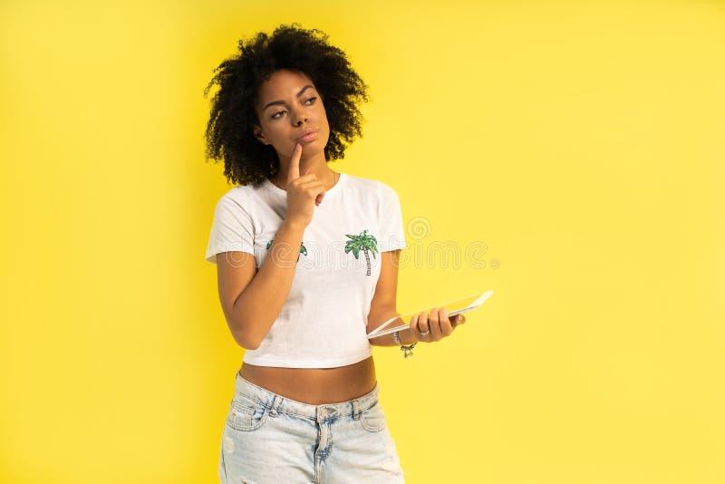 Vrij jonge afro Amerikaanse vrouw die die en tabletcomputer bevinden met behulp van over gele achtergrond wordt geïsoleerd stock afbeelding