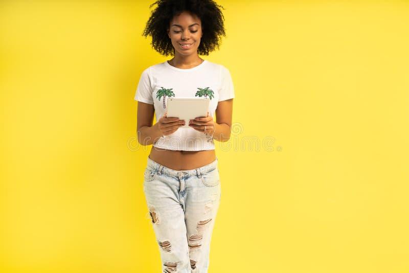 Vrij jonge afro Amerikaanse vrouw die die en tabletcomputer bevinden met behulp van over gele achtergrond wordt geïsoleerd stock foto