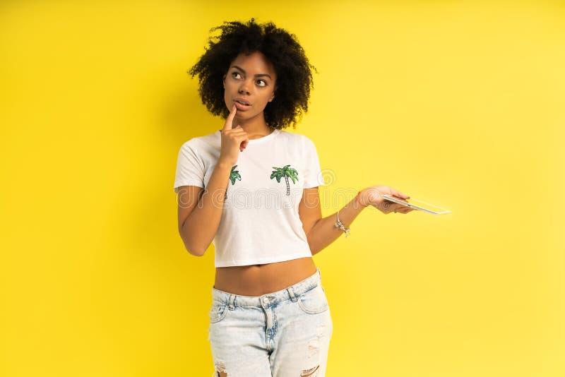 Vrij jonge afro Amerikaanse vrouw die die en tabletcomputer bevinden met behulp van over gele achtergrond wordt geïsoleerd royalty-vrije stock afbeeldingen