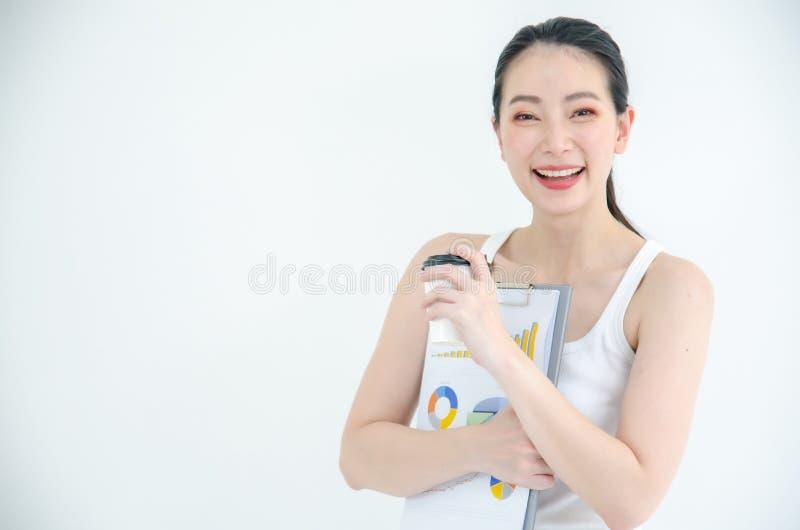 Vrij jonge Aziatische bedrijfsvrouw die een kop koffie en documentdossiers houden Ge?soleerd Studioportret op witte achtergrond royalty-vrije stock afbeelding