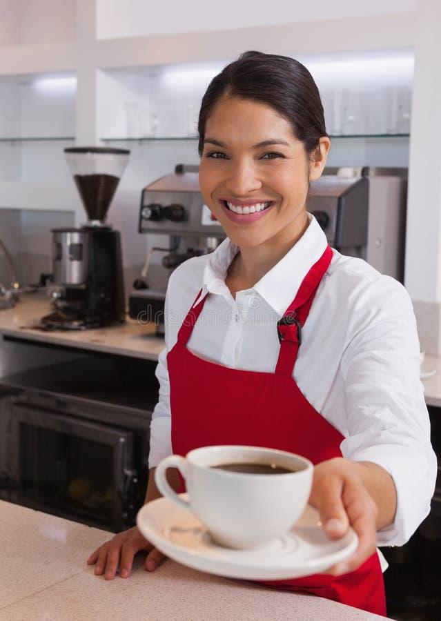 Vrij jonge barista die kop van koffie aanbieden die bij camera glimlachen stock foto's
