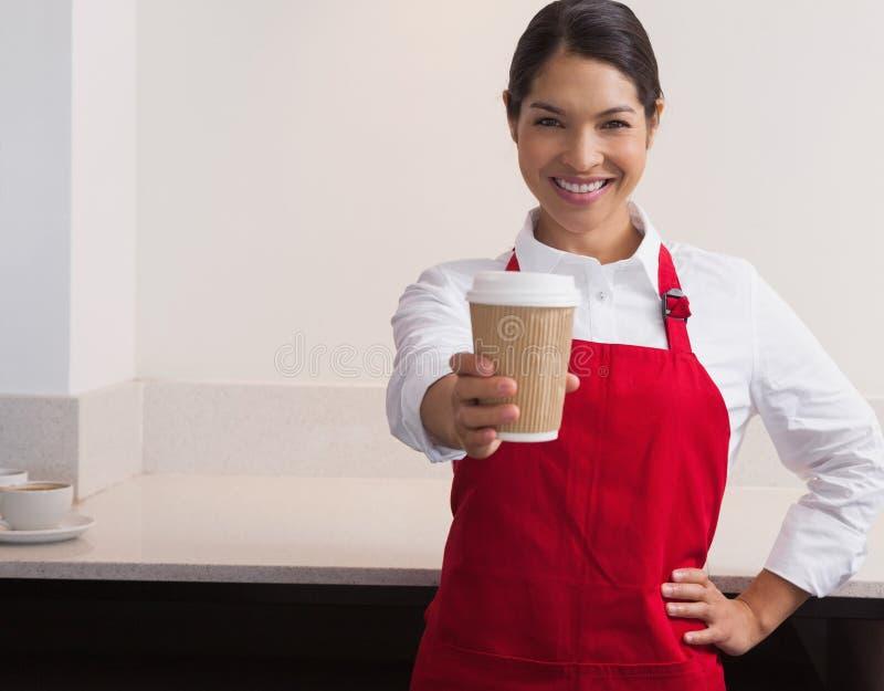 Vrij jonge barista die kop van koffie aanbieden gaan glimlachend bij camera stock fotografie