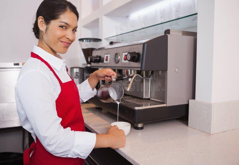 Vrij jonge barista gietende melk in kop van koffie die bij camera glimlachen stock foto