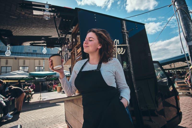 Vrij jonge barista heeft een onderbreking en het genieten van van koffie stock afbeelding