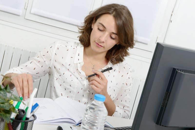 Vrij jonge bedrijfsvrouw die bij PC in bureau werken royalty-vrije stock afbeeldingen