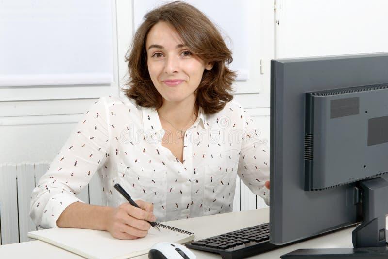 Vrij jonge bedrijfsvrouw die bij PC in bureau werken stock foto's