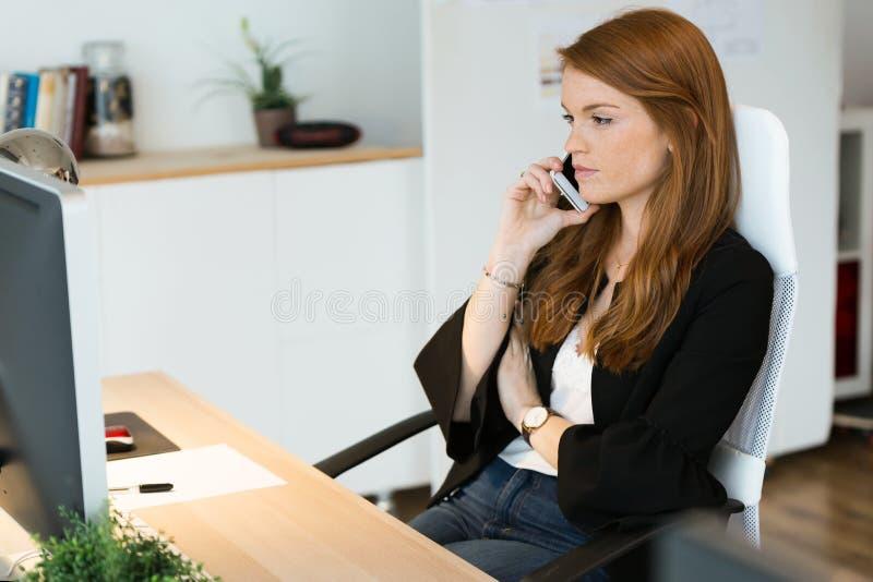 Vrij jonge bedrijfsvrouw die haar mobiele telefoon in het bureau met behulp van royalty-vrije stock afbeelding