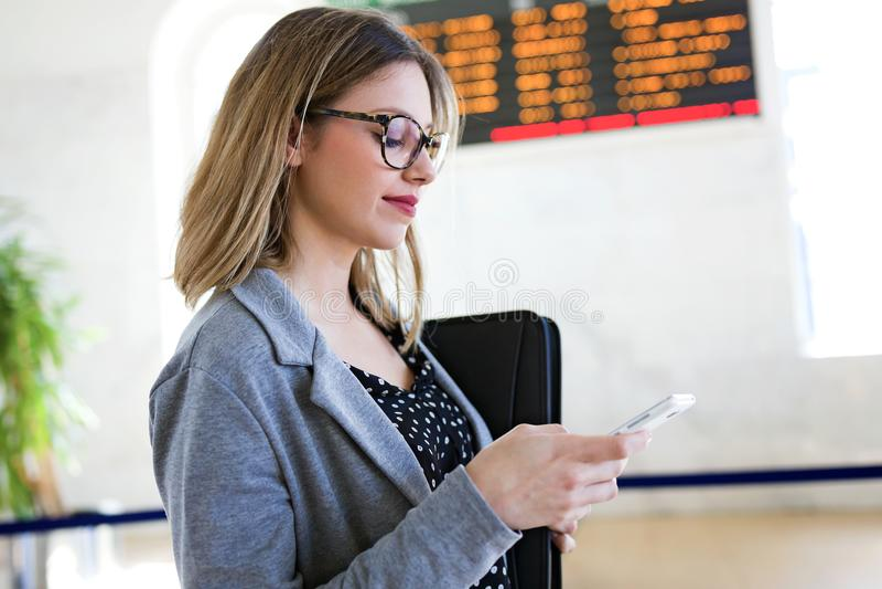 Vrij jonge bedrijfsvrouw die haar mobiele telefoon in het station met behulp van royalty-vrije stock afbeelding