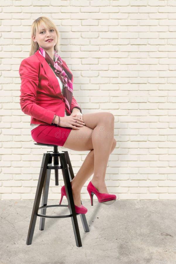 Vrij jonge blonde vrouw met een roze kostuum, die op een kruk zitten royalty-vrije stock fotografie