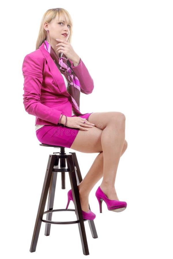 Vrij jonge blonde vrouw met een roze kostuum, die op een kruk zitten royalty-vrije stock afbeeldingen