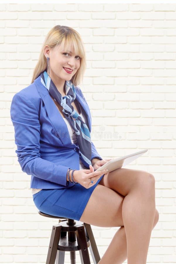 Vrij jonge blonde vrouw met tablet, die op een kruk zitten stock foto