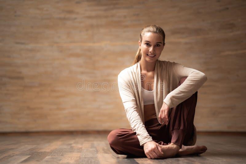 Vrij jonge damezitting op de vloer en het glimlachen royalty-vrije stock foto