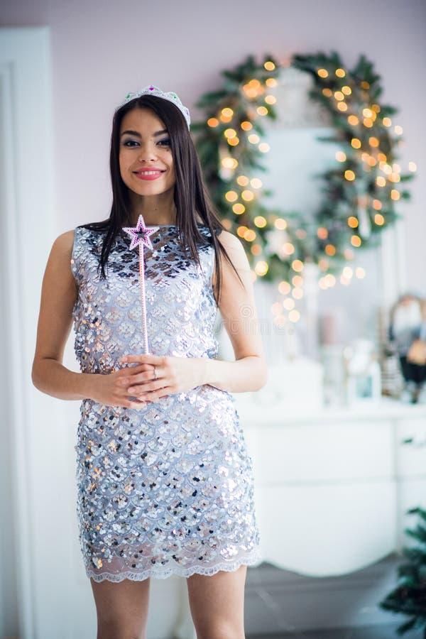 Vrij jonge donkerbruine vrouw die tegen Kerstmisachtergrond glimlachen met toverstokje in haar handen royalty-vrije stock afbeeldingen