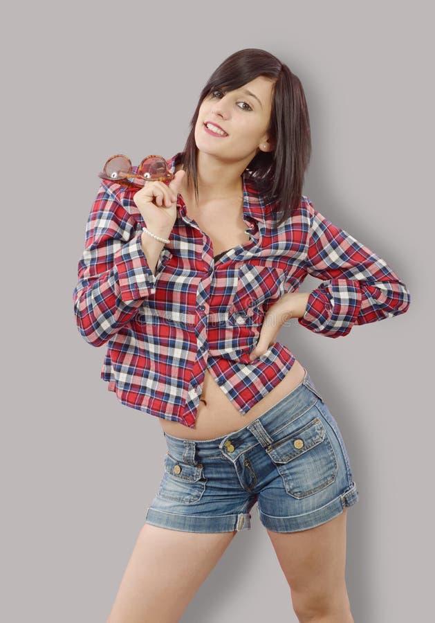 Vrij jonge donkerbruine vrouw met een geruit overhemd op grijze backg stock foto's