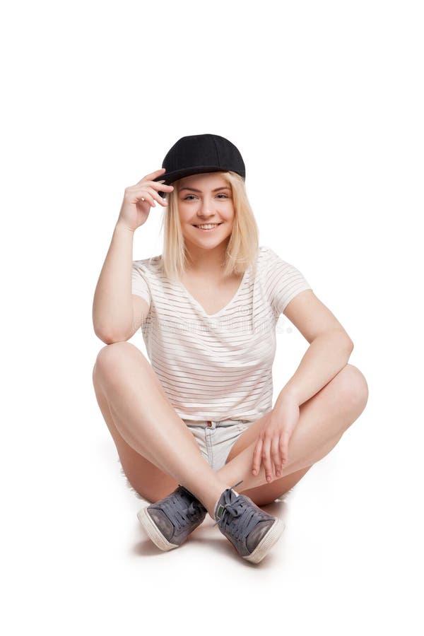 Vrij jonge geïsoleerde vrouwenzitting met gekruiste benen stock foto