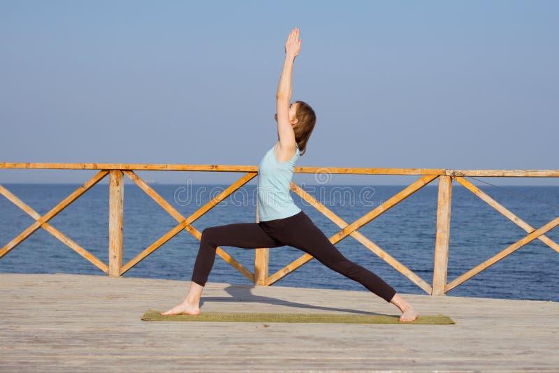 vrij jonge geschikte vrouw die yogaoefeningen op het de zomerstrand doen royalty-vrije stock foto's