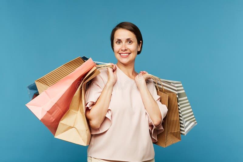 Vrij jonge glimlachende vrouwelijke klant met bos van papieren zakken stock foto