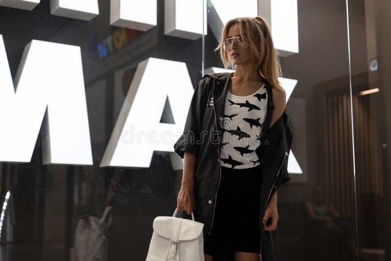 Vrij jonge hipstervrouw in in glazen in een witte t-shirt met een patroon in een de zomerlaag in een in rok stock foto
