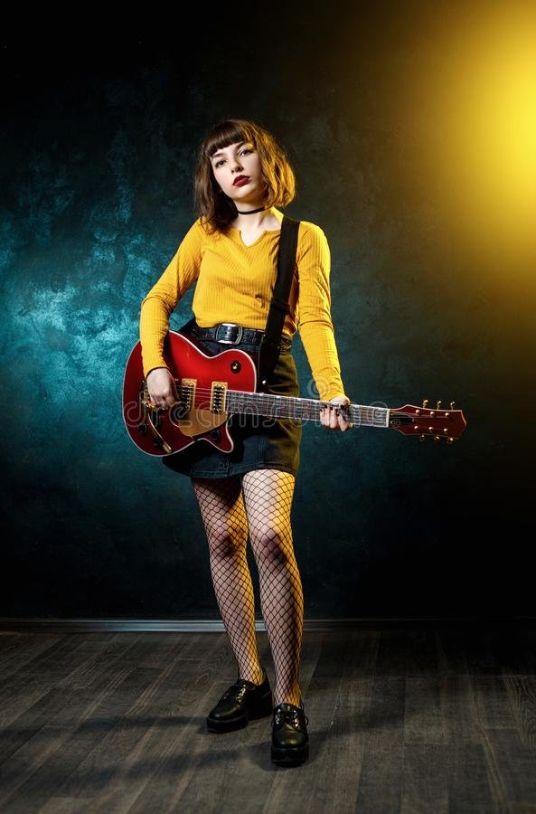 Vrij jonge hipstervrouw met krullend haar met rode gitaar in neonlichten De musicus van de rots speelt elektrogitaar stock afbeeldingen