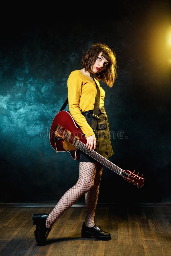 Vrij jonge hipstervrouw met krullend haar met rode gitaar in neonlichten De musicus van de rots speelt elektrogitaar royalty-vrije stock afbeelding