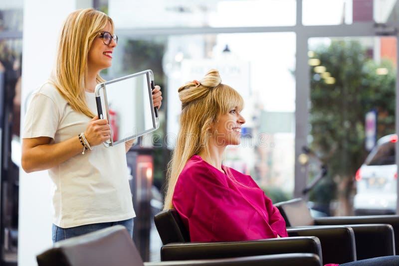 Vrij jonge kapper die het klaar kapsel van de vrouwelijke cliënt met spiegel in schoonheidssalon tonen stock foto